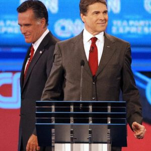 Republican presidential candidate former Massachusetts Gov. Mitt Romney, left, passes behind Texas Gov. Rick Perry during a break in a Republican presidential debate Monday, Sept. 12, 2011, in Tampa, Fla. (AP Photo/Mike Carlson)