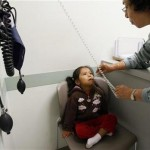 Uninsured patient Donaji Cruz, 3, has her blood pressure measured by hospital assistant Rosalinda Galvan during a health check-up at Venice Family Clinic in Venice, California. (REUTERS/Lucy Nicholson)