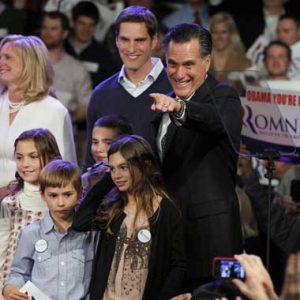 Former Massachusetts Gov. Mitt Romney surrounded by his family points towards supporters at the Romney for President New Hampshire primary night victory party at Southern New Hampshire University in Manchester, N.H., Tuesday. (AP Photo/Elise Amendola)