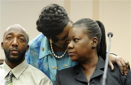 Tracy Martin (L) and Sybrina Fulton (R), parents of Florida shooting victim Trayvon Martin, are comforted by U.S. Representative Sheila Jackson Lee (D-TX) (2nd R) as they speak at a public forum on their son's case, on Capitol Hill in Washington.  (REUTERS/Jonathan Ernst)