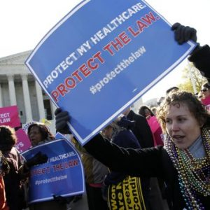 Lisa Dowling, from Arlington, Va., a supporter of health care reform, rallies in front of the Supreme Court in Washington, Tuesday, March 27, 2012, as the court continues arguments on the health care law signed by President Barack Obama. (AP Photo/Charles Dharapak)