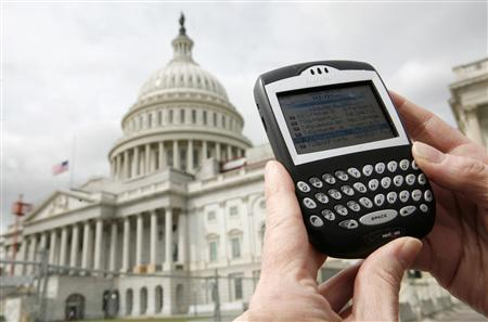 A journalist checks her Blackberry communication device on Capitol Hill. (REUTERS/Jim Young/Files)