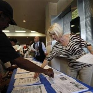 Carlene Gepner of WorkSource hands out job applications at the 11th annual Skid Row Career Fair the Los Angeles Mission in Los Angeles, California, May 31, 2012. 
