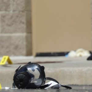Yellow markers sit next to evidence, including a gas mask, as police investigate the scene outside the Century 16 movie theater east of the Aurora Mall in Aurora, Colo. on Friday.  (AP Photo/David Zalubowski) (AP Photo/David Zalubowski)