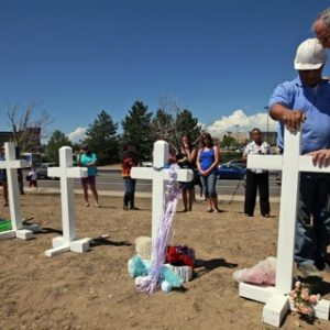Aurora, Colo. Mayor Steve Hogan, right, says a prayer with Greg Zanis, from Aurora, Ill., as Zanis places crosses for the shooting victims across the street from the Century 16 movie theater in Aurora, Colo. on Sunday.
