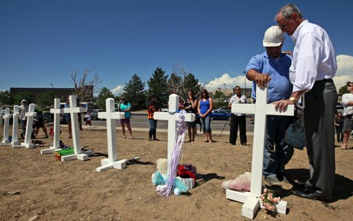 Aurora, Colo. Mayor Steve Hogan, right, says a prayer with Greg Zanis, from Aurora, Ill., as Zanis places crosses for the shooting victims across the street from the Century 16 movie theater in Aurora, Colo. on Sunday.  (AP Photo/Alex Brandon)