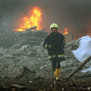 A firefighter runs through the blast site after a garbage truck exploded near a hotel used by western contractors in central Baghdad, Iraq. In the first tally of its kind, a federal investigative agency has calculated that at least 719 people, nearly half of them Americans, were killed working on projects to rebuild Iraq following the U.S. invasion in 2003. (AP Photo/Hadi Mizban/file)