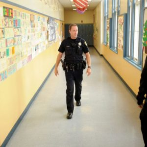 Officer Rick Moore of the Oakland school district police patrols Oakland Technical High School in Oakland, Calif. The National Rifle Association on Friday, Dec. 21 2012 called for the placement of an armed police officer in every school, but parents and educators questioned how safe such a move would keep kids, whether it would be economically feasible and how it would alter student life. Their reactions ranged from supportive to disgusted. (AP Photo/Noah Berger, File)