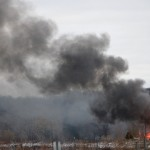 Homes burn on Lake Road, Monday, Dec. 24, 2012 in Webster, New York. A former convict set a house and car ablaze in his lakeside New York state neighborhood to lure firefighters then opened fire on them, killing two and engaging police in a shootout before killing himself while several homes burned. Authorities used an armored vehicle to evacuate the area. (AP Photo/Democrat & Chronicle, Max Schulte)