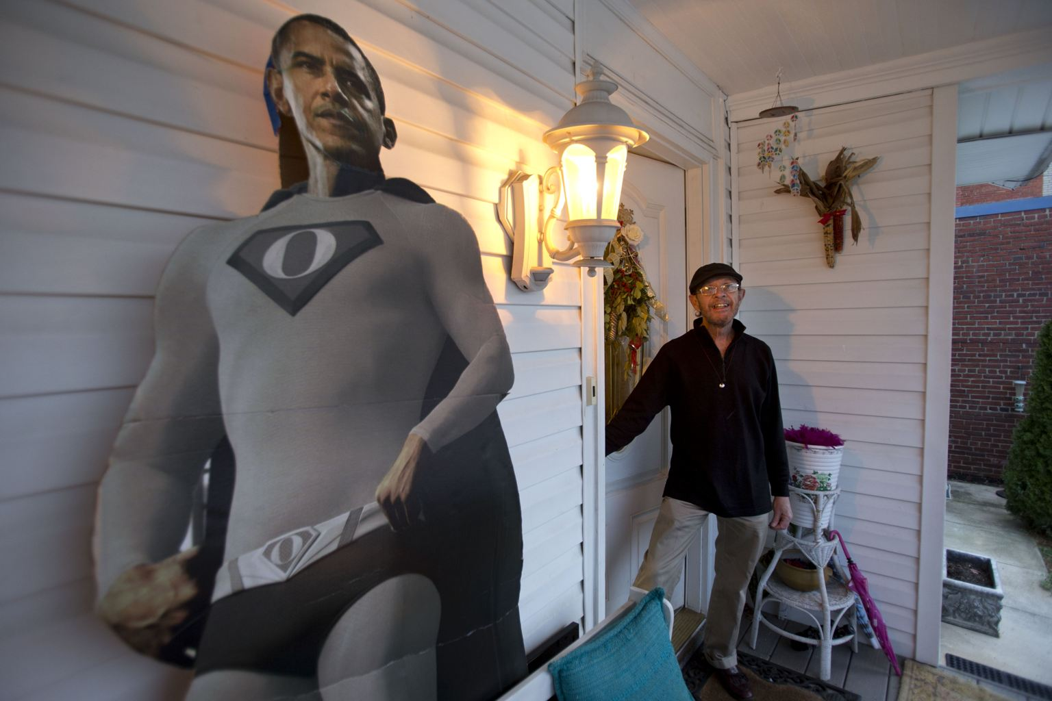 In this Thursday, Dec. 20, 2012, photo, Bernard Duval, innkeeper of the Aunt Bee's Little White House B&B, stands in the doorway by a cutout of President Barack Obama in a super hero outfit, at the B&B in Washington. The six-room bed and breakfast in northeast Washington still had two rooms available for the presidential inauguration as of the week before Christmas, with rates starting at $225 a night. (AP Photo/Jacquelyn Martin)