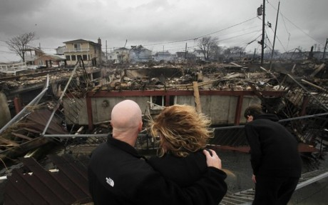Robert Connolly, left, embraces his wife Laura as they survey the remains of the home owned by her parents that burned to the ground in the Breezy Point section of New York, during Superstorm Sandy. (AP Photo/Mark Lennihan, File)