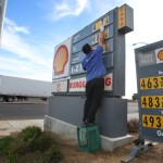 Luis Cuevas changes the gas prices at the Shell station off California State Route 99. Forecasters say that ample oil supplies and weak U.S. gasoline demand will keep a lid on prices in 2103. The lows will be lower, the highs won't be so high, and the average price of a gallon of gasoline will fall 5 percent to $3.44, according to the Energy Department.  (AP Photo/Gary Kazanjian, File)