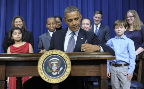 President Barack Obama, accompanied by children who wrote the president about gun violence following last month's shooting at an elementary school in Newtown, Conn., signs executive orders, Wednesday, Jan. 16, 2013, in the South Court Auditorium at the White House in Washington. The children and their parents from left, Hinna Zeejah, 8, and Nadia Zeejah, Hinna's mother, Taejah Goode, 10, and Kimberly Graves, Taejah's mother, Julia Stokes, 11, and Dr. Theophil Stokes, Julia's father, and Grant Fritz, 8, and Elisabeth Carlin, Grant's mother. (AP Photo/Susan Walsh)