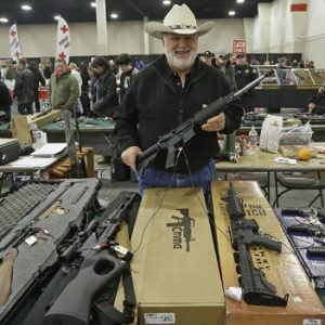 "Ken Haiterman, of Pioneer Market, holds a CMMG 5.56mm AR 15 during the 2013 Rocky Mountain Gun Show in Sandy, Utah. A bipartisan quartet of senators, including two National Rifle Association members and two with ""F"" ratings from the potent firearms lobby, are quietly trying to reach compromise on expanding the requirement for gun-sale background checks. (AP Photo/Rick Bowmer, File)"
