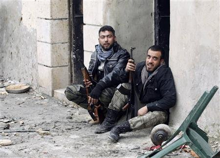 Free Syrian Army fighters carry their weapons as they sit on the ground at the Sheikh Saeed district, near a cement factory in Aleppo, February 7, 2013.  REUTERS/Zain Karam