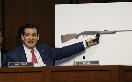 U.S. Senator Ted Cruz, (R-TX), holds a plastic hand grip in front of a picture of a hunting rifle as he questions NRA CEO Wayne LaPierre (not in photo) about the effect of proposed gun control legislation during a hearing held by the Senate Judiciary committee on Capitol Hill in Washington.  (REUTERS/Kevin Lamarque)