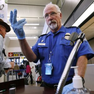 TSA officer Robert Howard signals an airline passenger forward at a security check-point at Seattle-Tacoma International Airport in SeaTac, Wash. Flight attendants, pilots, federal air marshals and even insurance companies are part of a growing backlash to the Transportation Security Administration's new policy allowing passengers to carry small knives and sports equipment like souvenir baseball bats and golf clubs onto planes.  (AP Photo/Elaine Thompson, File)