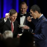 David H. Petraeus, former army general and head of the Central Intelligence Agency, tastes a ceremonial cake presented to him by Hector Sandoval, a member of the USC ROTC program, at the annual dinner for veterans and ROTC students at the Univeristy of Southern California, in downtown Los Angeles Tuesday.  (AP Photo/Reed Saxon)