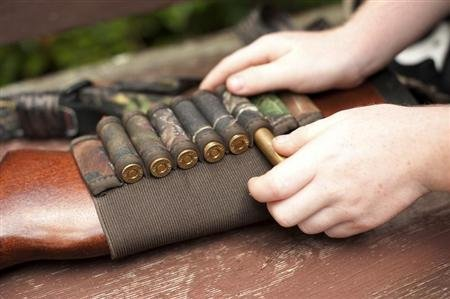 A 6-year-old boy prepares a gun before a hunt near Union Springs, Alabama. REUTERS/Michael Spooneybarger