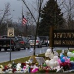 Cars drive below a U.S. flag at half mast and past a memorial outside the entrance to Newtown High School in Newtown, Connecticut. REUTERS/Lucas Jackson