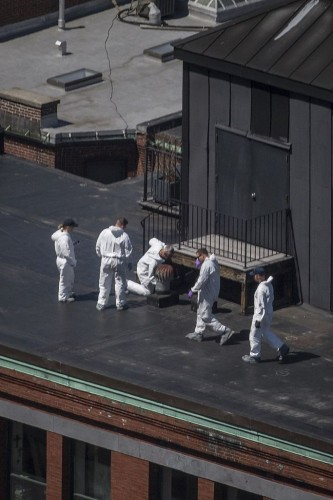 Investigators search for evidence on the rooftop of a building located above the site of a bomb blast on Boylston Street two-days after multiple explosions at the Boston Marathon killed three and injured 176 in Boston, Massachusetts April 17, 2013. Investigators believe they have identified a suspect in the Boston marathon bombing from security video, a U.S. law enforcement source said. REUTERS/Adrees Latif