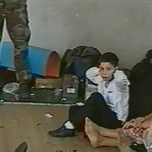Hostages sit on a floor in a gym as a hostage-taker stands with his left foot on a book apparently with a device connected to a chain of explosives in the school in Beslan, Russia taken in this undated image from television during the early part of the siege which began on Sept. 1, 2004 and ended with over 300 people dead.. (AP Photo/NTV-Russian Television Channel, File)
