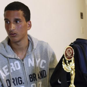 Salah Eddin Barhoum sits in his apartment in Revere, Mass., Thursday, April 18, 2013, with one of the trophies he won in an athletic competition, and the bag he was carrying on Monday near the finish line of the Boston Marathon. The 17-year-old from Morocco, whose photograph appeared on the front page of the New York Post in connection with the Boston Marathon bombings, told The Associated Press he has been scared to go outside because he worries people will blame him for Monday's attack. (AP Photo/Rodrique Ngowi)