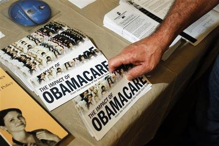 "A Tea Party member reaches for a pamphlet titled ""The Impact of Obamacare"", at a ""Food for Free Minds Tea Party Rally"" in Littleton, New Hampshire October 27, 2012. REUTERS/Jessica Rinaldi"