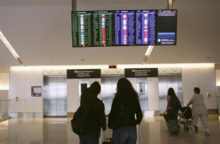 Airline passengers look at a flight status board at San Francisco International Airport in San Francisco, California. REUTERS/Robert Galbraith