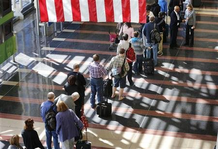 A long line of passengers wait to enter the security checkpoint before boarding their aircraft at Reagan National Airport in Washington.  (REUTERS/Larry Downing)