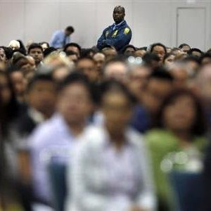 A security guard stands guard near immigrants during a naturalization ceremony in Los Angeles.. (REUTERS/Lucy Nicholson)