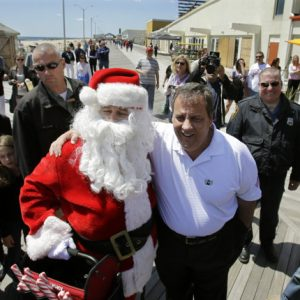 New Jersey Gov. Chris Christie, center right, poses for a photograph with Paul Tremitiedi, as Santa, of Jersey City, Sunday, May 26, 2013, during a visit to the boardwalk in Asbury Park, N.J. The first summer season after Superstorm Sandy is underway at the Jersey shore, parts of which were devastated by the October storm. This is a brand-new Jersey Shore. While some recovery is still ongoing from Superstorm Sandy, the Jersey Shore to a very large extent has been cleaned up, rebuilt, reopened and is ready for business. (AP Photo/Mel Evans)