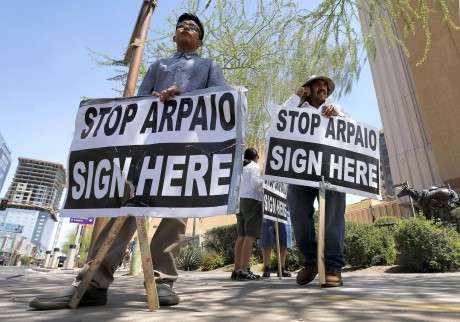 Simon Lopez, left, and Hiliaro Islas hold signs while trying to collect signatures in an effort to recall Maricopa County Sheriff Joe Arpaio, Wednesday, May 29, 2013 in downtown Phoenix.  (AP Photo/Matt York)