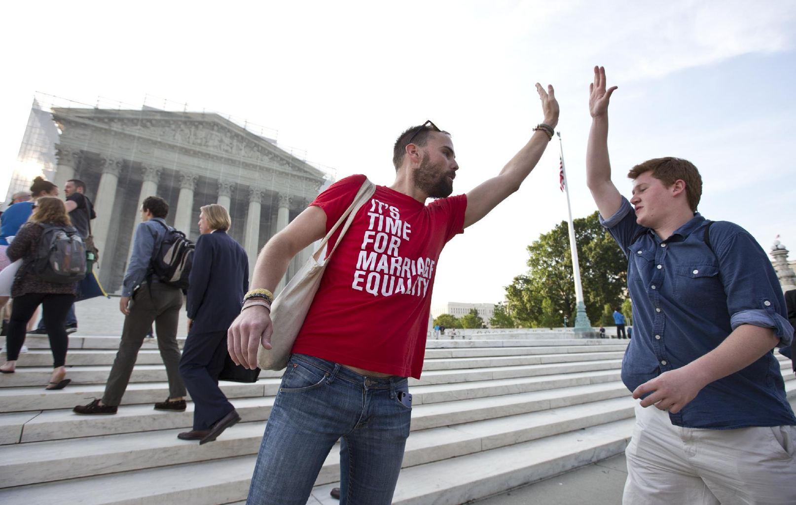 Gay rights activist Bryce Romero, who works for the Human Rights Campaign, offers an enthusiastic high-five to visitors getting in line to enter the Supreme Court on a day when justices are expected to hand down major rulings on two gay marriage cases that could impact same-sex couples across the country, in Washington, Wednesday. (AP Photo/J. Scott Applewhite)