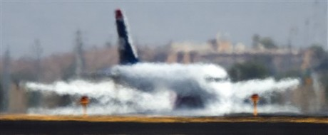 A jet looks like it is melting into the runway as it is distorted by the heat waves rising up from the north runway at Sky Harbor International Airport, Friday, June 28, 2013, the hottest day of the year so far. (AP Photo/The Arizona Republic, Tom Tingle)