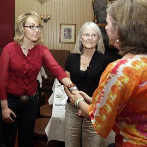 Former Arizona Rep. Gabrielle Giffords greets Jackie Barden, right, mother of a Sandy Hook Elementary School shooting victim Daniel Barden, as local supporter Mary Ann Sosnoff, center, looks on at the Orchard Street Chop Shop in Dover, N.H.  Three years after being shot in the head, Giffords is in New Hampshire to urge support for background checks on gun purchases. (AP Photo/Mary Schwalm)