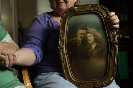 "In this photo taken Monday, July 1, 2013, in Chapel Hill, N.C., Shelia Reese, right, holds hands with her mother Chris Tench while holding a portrait of Tench and her father Kenneth F. Reese, a soldier who is still Missing In Action from the Korean War. Tench, who was later remarried, has never known what happened to her husband. The Pentagon's effort to account for tens of thousands of Americans missing in action from foreign wars is so inept, mismanaged and wasteful that it risks descending from ""dysfunction to total failure,"" according to an internal study suppressed by military officials. (AP Photo/Gerry Broome)"