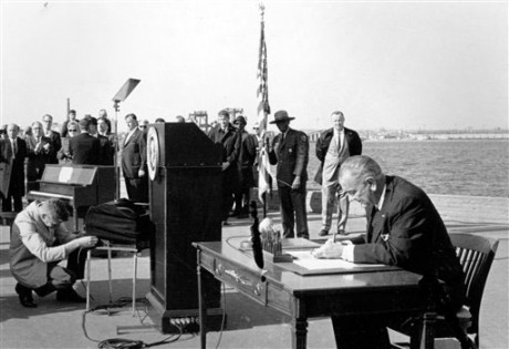 U.S. President Lyndon B. Johnson sits at his desk on Liberty Island in New York Harbor as he signs a new immigration bill. It was in 1965 that the U.S. government radically changed its immigration policy, and planted the seeds for America's current demographic explosion, a shift that historians say happened in part because of a hunger for change and equality created by the civil rights movement. (AP Photo)