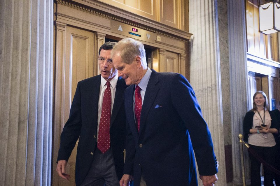 Sen. John Barrasso, R-Wyo., left, and Sen. Bill Nelson, D-Fla., right, arrive for the Senate to vote on a bill to fund the government. (AP Photo/J. Scott Applewhite)