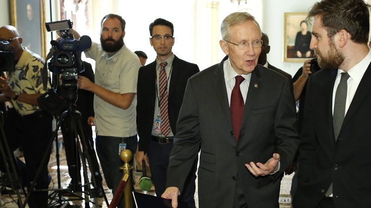 Senate Majority Leader Harry Reid (D-NV) (2nd R) talks with an aide as he walks to a Senate Democratic caucus meeting at the U.S. Capitol. (REUTERS/Jonathan Ernst )