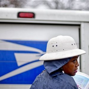 Postal Service letter carrier Jamesa Euler, delivers mail in the rain in the Cabbagetown neighborhood, in Atlanta. (AP Photo/David Goldman)
