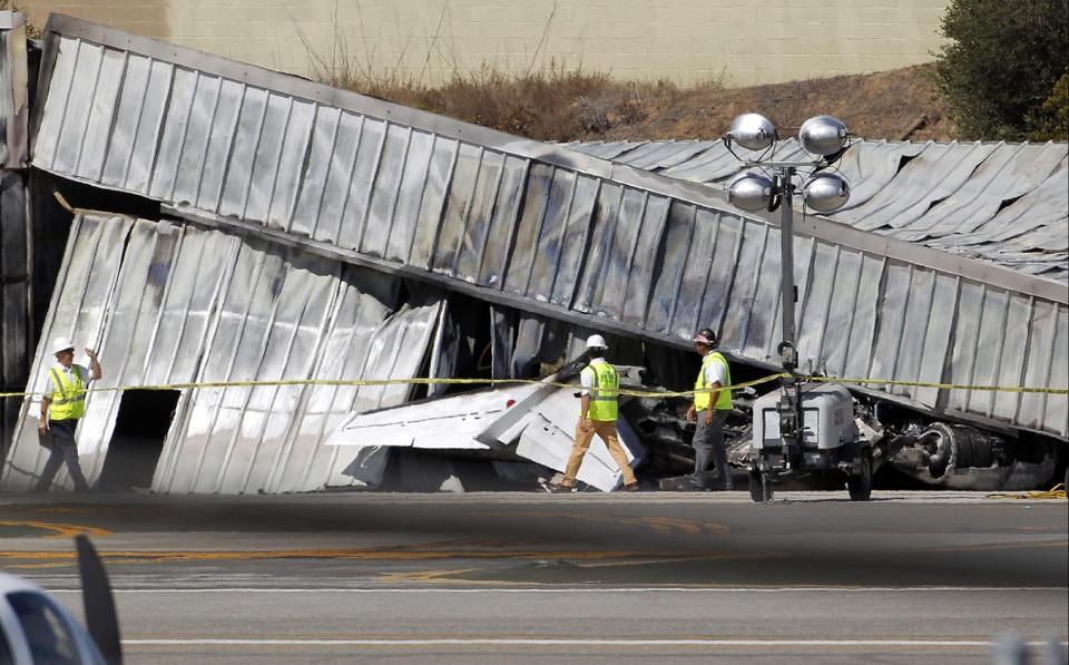 Investigators stand near a hanger at the site of a plane crash in Santa Monica, Calif. Monday. (AP Photo/Nick Ut)