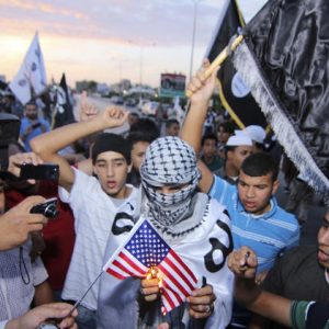 Dozens of supporters of the militant group, Ansar al-Shariah, burn an American flag and shout anti-American slogans denouncing the U.S. violation of Libya's sovereignty in the abduction of Abu Anas al-Libi, in the center of Benghazi, Libya, (AP Photo/Mohammed el-Shaiky)