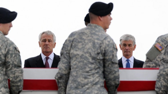 Defense Secretary Chuck Hagel, left, and Army Secretary John McHugh, right, watch an Army carry team move a transfer case containing the remains of Pfc. Cody J. Patterson Wednesday at Dover Air Force Base, Del. (AP Photo/Steve Ruark)