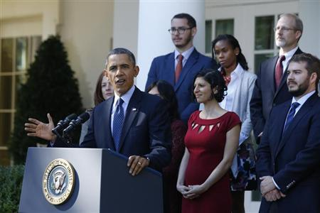 President Barack Obama stands with Affordable Care act registrants and beneficiaries as he speaks about healthcare from the Rose Garden of the White House.  (REUTERS/Jason Reed)