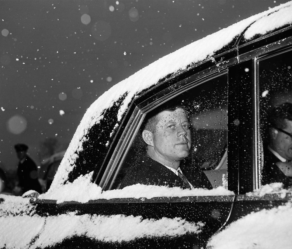 President John F. Kenendy in his snow-covered limousine at Andrews Air Force Base in 1961. (AP/Byron Rollins)