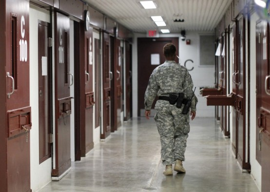 A guard walks through a cellblock inside Camp V, a prison used to house detainees at Guantanamo Bay U.S. Naval Base. (REUTERS/Bob Strong)