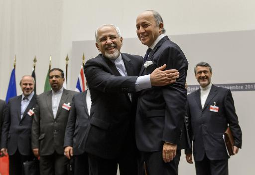 Iranian Foreign Minister Mohammad Javad Zarif (left) hugs his French counterpart Laurent Fabius after a landmark deal in Geneva, (AFP, Fabrice Coffrini)