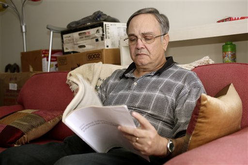 "Howard Kraft looks over healthcare information in his Lincolnton, N.C. home Monday."" (AP Photo/Nell Redmond)"