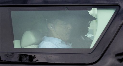President Barack Obama is seen through the window of his motorcade vehicle as he is driven through the Kailua, Hawaii, neighborhood where he is spending his annual holiday vacation with his family,. (AP Photo/Carolyn Kaster)